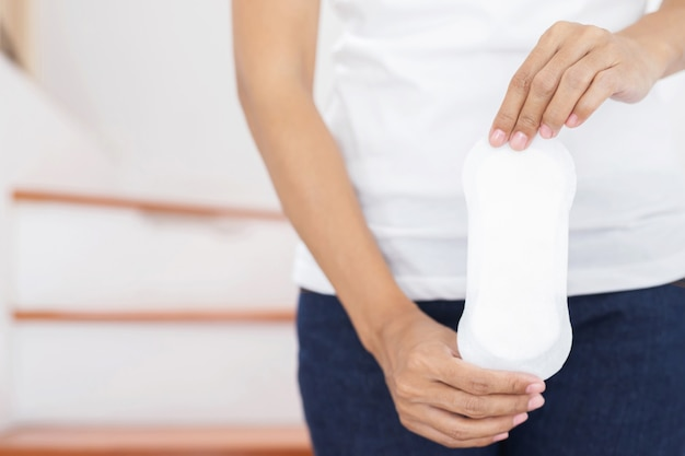 Female hygiene. close up young woman holding a clean period slim sanitary napkin pad.
