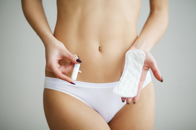 Female hygiene. closeup of beautiful woman with fit slim body in white underwear holding sanitary towel, panty liner in hands. girl holding clean period pad, feminine intimate product.
