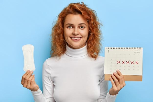 女性の衛生の概念。赤毛の笑顔の女性は、清潔な期間の生理用ナプキンパッドと月経カレンダーを保持しています