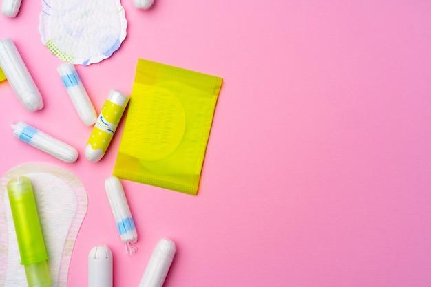 ピンクの背景に女性の衛生パッドとタンポン