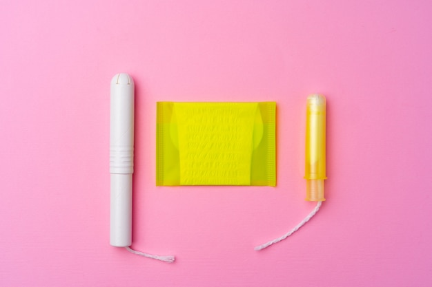Female hygienic pad and tampons on pink background top view