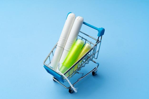 青い上のショッピングカートの女性の衛生的なタンポンのクローズアップ