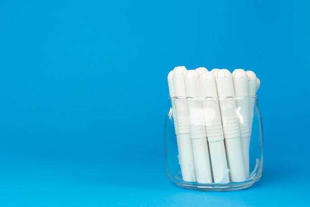 紙の表面の女性の衛生的なタンポンをクローズアップ