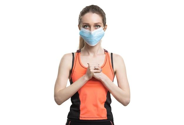 検疫中にワークアウトするフェイスマスクとオレンジ色のスポーツスーツの女性