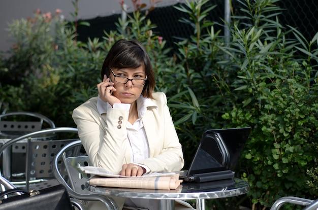 녹색 숲 근처에 그녀의 노트북과 함께 테이블에 앉아 흰색 정장 여성