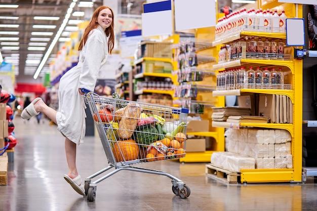 Женщина в халате наслаждается покупками в супермаркете, неся тележку, полную продуктов, в продуктовом магазине, улыбается