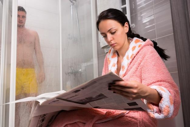 목욕 가운을 입은 여성이 신문을 읽고 남자 친구가 욕실에 투명한 유리 문이 있는 샤워실에서 샤워를 하는 동안 남자 친구를 기다리고 있습니다.