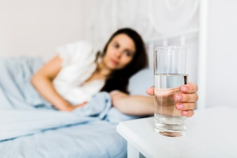 Female in bed holding glass of water