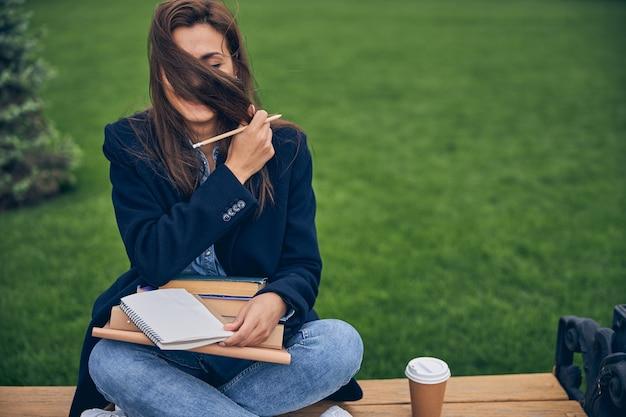 벤치에 앉아 공부하는 동안 길고 검은 머리카락으로 그녀의 얼굴을 숨기는 캐주얼 옷을 입은 여성