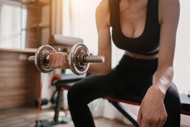 Женщина в снаряжении для упражнений с гантелями, фитнесом, тренировкой, домашними упражнениями, образом жизни и здоровой концепцией.