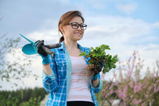 딸기 부시를 들고 정원 도구와 장갑에 여성