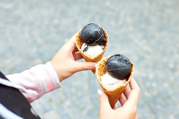 Женщина в руке уголь и ванильное мороженое