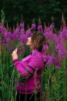 牧草地の花に囲まれたパーカーの女性