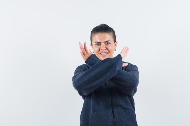 停止ジェスチャーをして自信を持って見えるパーカーの女性、正面図。
