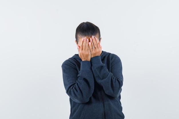Женщина в толстовке с капюшоном, взявшись за руки на лице и выглядя испуганной, вид спереди.