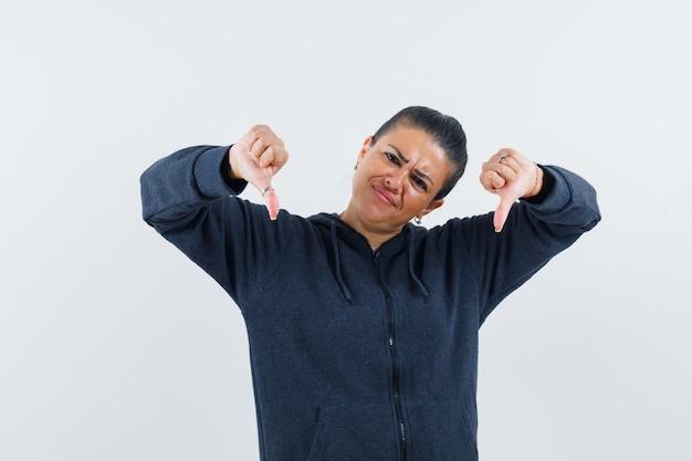 Женщина в толстовке с капюшоном показывает палец вниз и недовольна, вид спереди.