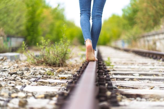 裸足で電車のレールを歩くジーンズの女性