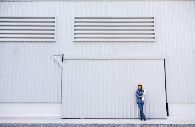 建設現場で金属板壁の前面に黄色の安全帽子をかぶったジーンズの女性