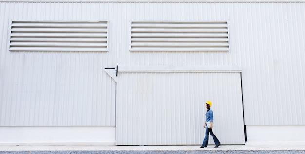 건설 현장에서 금속 시트 벽의 노란색 안전 모자 앞을 입고 청바지 여성