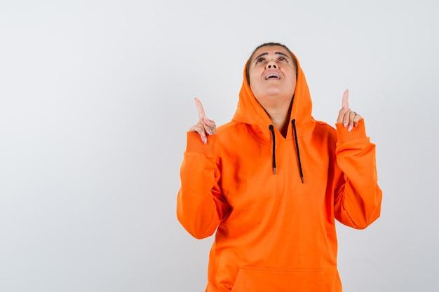 オレンジ色のパーカーの女性が上向きで希望に満ちている
