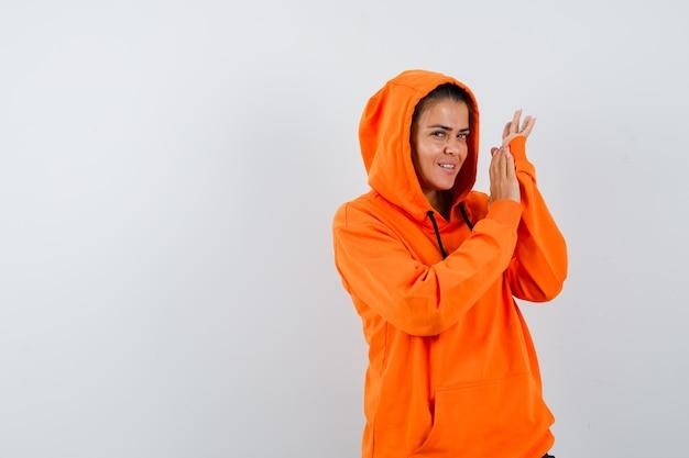 オレンジ色のパーカーの女性が立って魅力的に見ながらポーズをとる