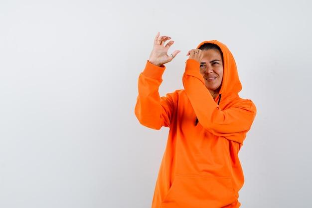 望遠鏡を持っているふりをして自信を持って見えるオレンジ色のパーカーの女性