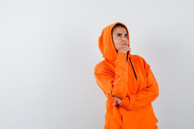 手に顎を支え、思慮深く見えるオレンジ色のパーカーの女性