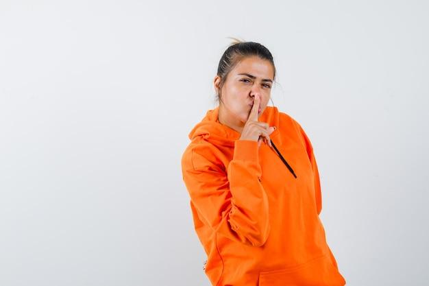 沈黙のジェスチャーを示し、賢明に見えるオレンジ色のパーカーの女性