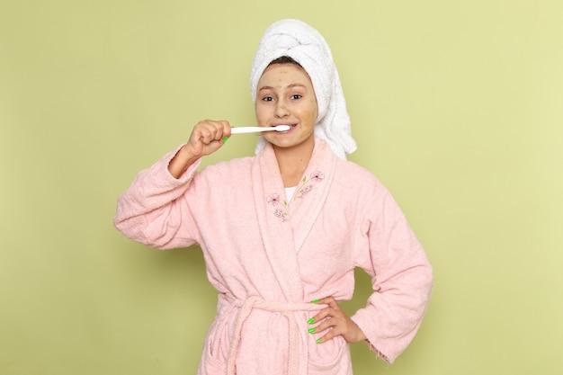 ピンクのバスローブの女性は彼女の歯をきれいに