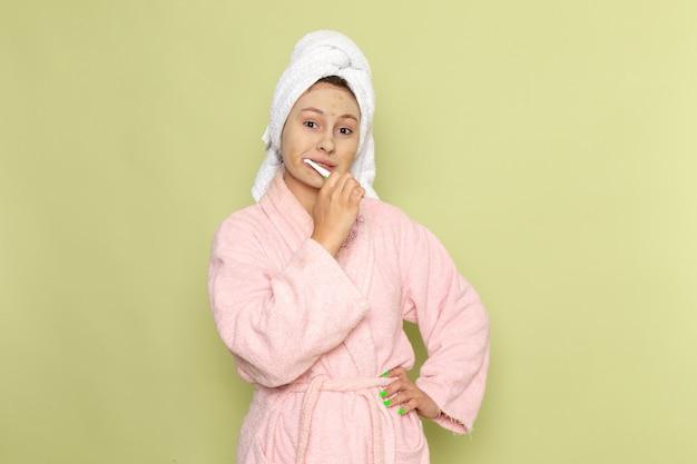 그녀의 이빨을 청소하는 분홍색 목욕 가운에 여성