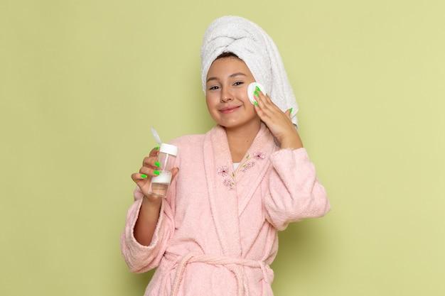 彼女の顔からすべての化粧をきれいにするピンクのバスローブの女性