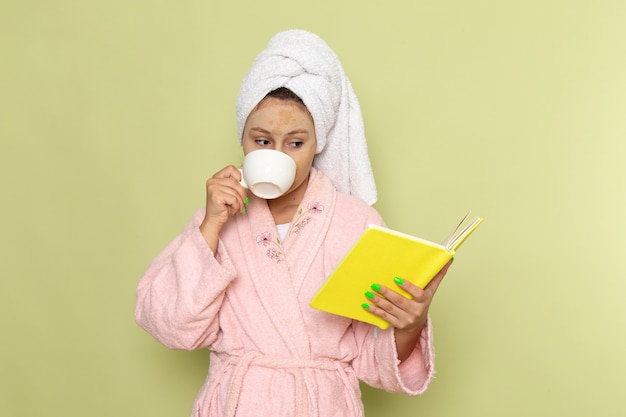 Женщина в розовом халате пьет кофе и читает книгу