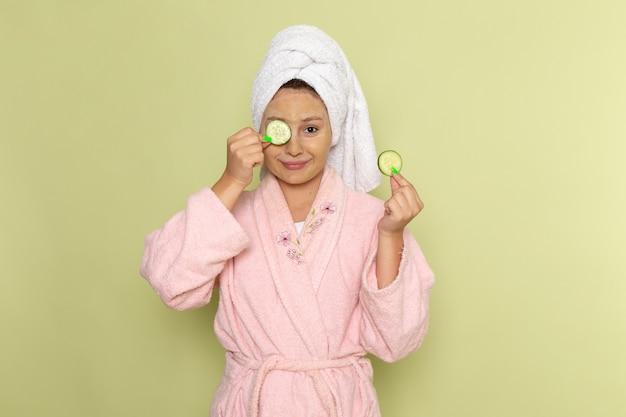 キュウリの指輪を保持しているピンクのバスローブの女性