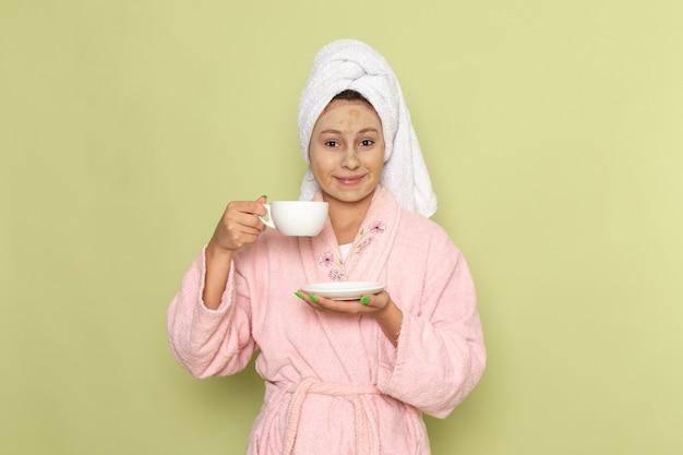 一杯のコーヒーを保持しているピンクのバスローブの女性
