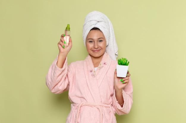 Женщина в розовом халате держит маленький спрей и растение
