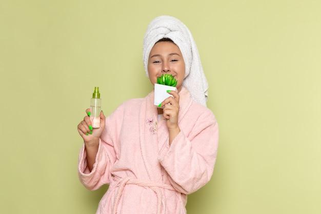 Женщина в розовом халате держит флакон со спреем для макияжа и растение