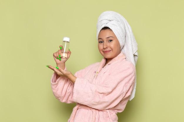 Женщина в розовом халате держит флакон с распылителем