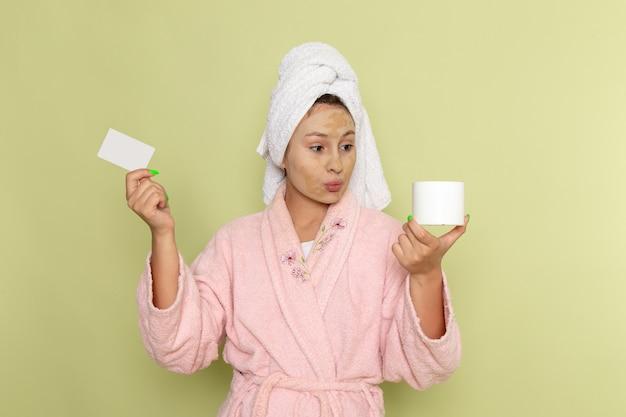 白いカードとクリームを保持しているピンクのバスローブの女性