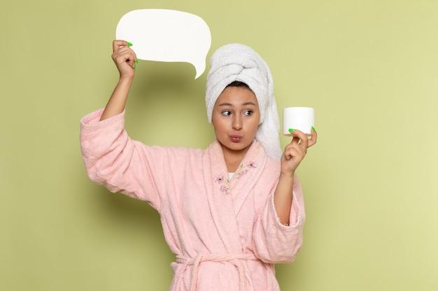 白い看板とクリームを保持しているピンクのバスローブの女性