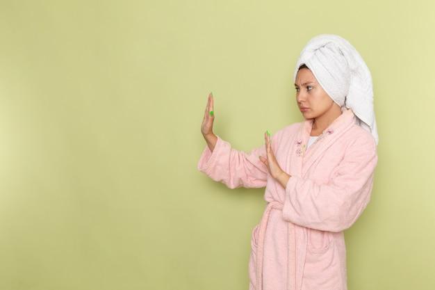慎重にポーズをとってピンクのバスローブの女性