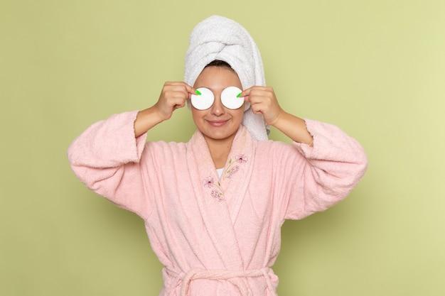 ピンクのバスローブを笑顔で目を綿で覆う女性