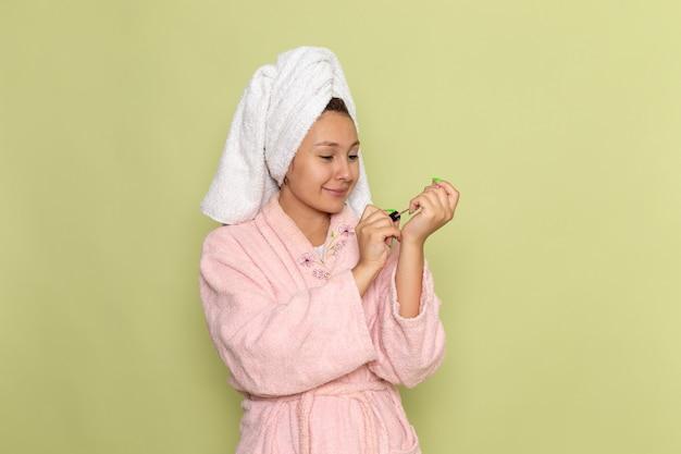 Женщина в розовом халате улыбается и поправляет ногти