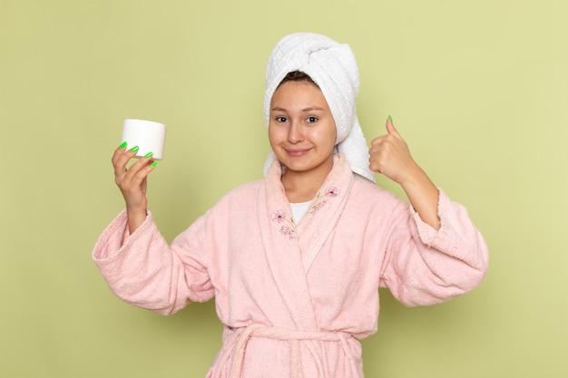 ピンクのバスローブ笑顔とholdignホワイトクリームの女性
