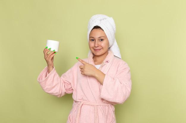 笑顔とクリームを保持しているピンクのバスローブの女性