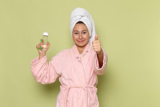 スプレーフラスコを保持している彼女の顔に笑顔でピンクのバスローブの女性