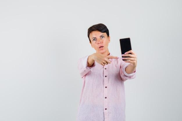 휴대 전화를 가리키고 의아해, 전면보기를 찾고 분홍색 셔츠에 여성.
