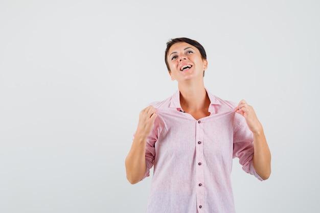 ピンクのシャツを着た女性がシャツを引っ張って誇らしげに見える、正面図。
