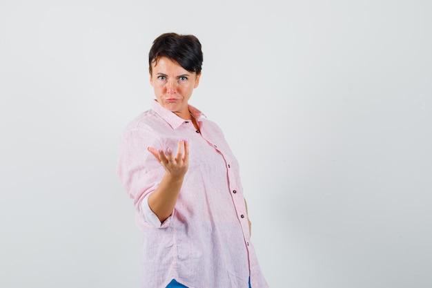 의아해 제스처, 전면보기에서 손을 스트레칭 분홍색 셔츠에 여성.