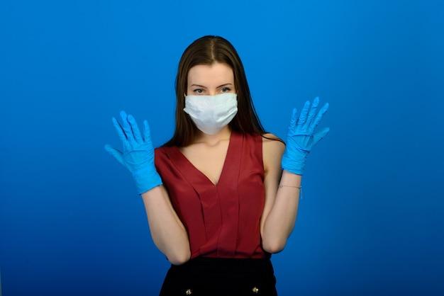 파란색 배경에 보호 의료 마스크와 파란색 장갑을 낀 여성.