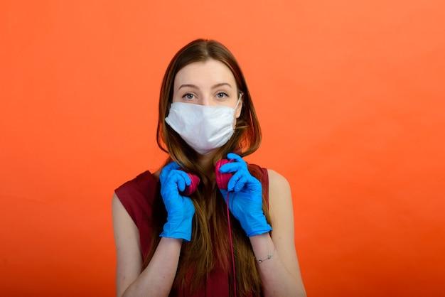 빨간색 배경에 보호 의료 마스크와 파란색 장갑을 낀 여성.